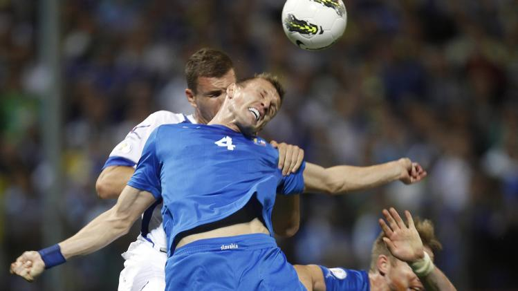 Bosnia's Dzeko fights for the ball with Slovakia's Durica during their 2014 World Cup qualifying match in Zenica