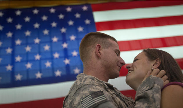 Spc. Whit Oakes, 21, left, of Tampa, Fla., with the U.S. Army's 4th Brigade Combat Team, 101st Airborne Division, embraces his girlfriend Lauren Anderson, 21, of Port St. Lucie, Fla. upon his unit's r