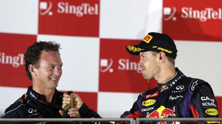 Red Bull team principal Horner celebrates on the podium with Red Bull Formula One driver Vettel after the Singapore F1 Grand Prix in Singapore