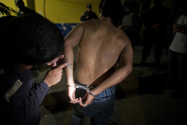 In this March 8, 2012 photo, a police officer inspects tattoos on a Mara Salvatrucha gang member Jose Alexander Carranza after his arrest in San Pedro Sula, Honduras.  A wave of violence has made Hond