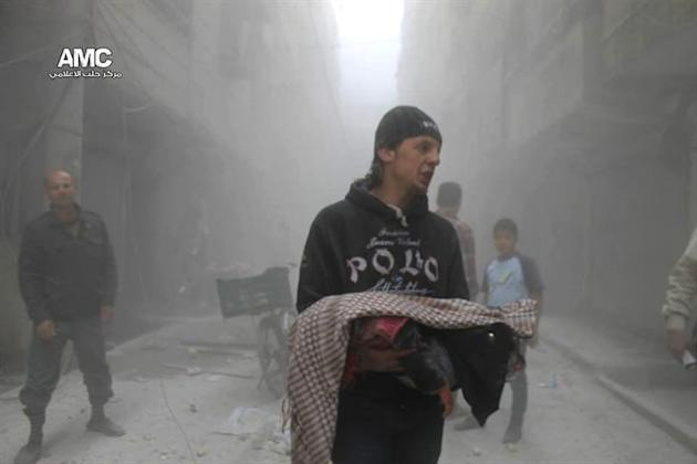 This photo provided by the anti-government activist group Aleppo Media Center (AMC), which has been authenticated based on its contents and other AP reporting, shows a Syrian man carrying the body of