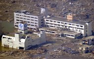 A hospital, back, struck by a deadly tsunami stands in Minamisanriku, Miyagi prefecture, northern Japan, Sunday, March 13, 2011, two days after a powerful earthquake-triggered tsunami hit the country's east coast.