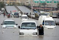A Syrian man pushes his car after it stopped in a flooded avenue following heavy rain in the northern Syrian city of Aleppo. Syria's army and main rebel force said they will cease fire on Friday, in line with an internationally backed truce during a Muslim holiday, but both reserved the right to respond to any aggression