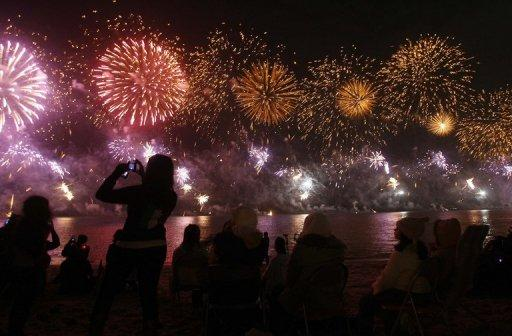 People take pictures of fireworks in Kuwait City