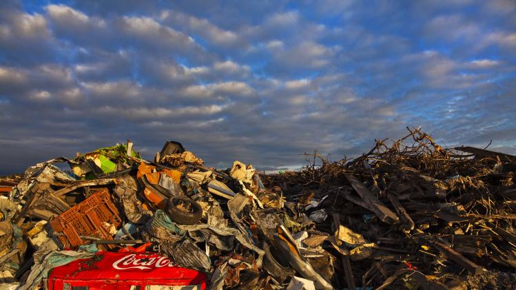 In this July 24, 2011 photo, debris lies in heaps after the tsunami swept inland across the contaminated town of Namie, Japan, and covers an area where a residential neighborhood once stood. (AP Photo/AP Photographer David Guttenfelder on assignment for National Geographic Magazine)