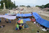 Residents rest at a temporary camp in front of the ruins of the 180-year-old Our lady of light Church on the island of Bohol, central Philippines, on October 16, 2013 after a huge earthquake