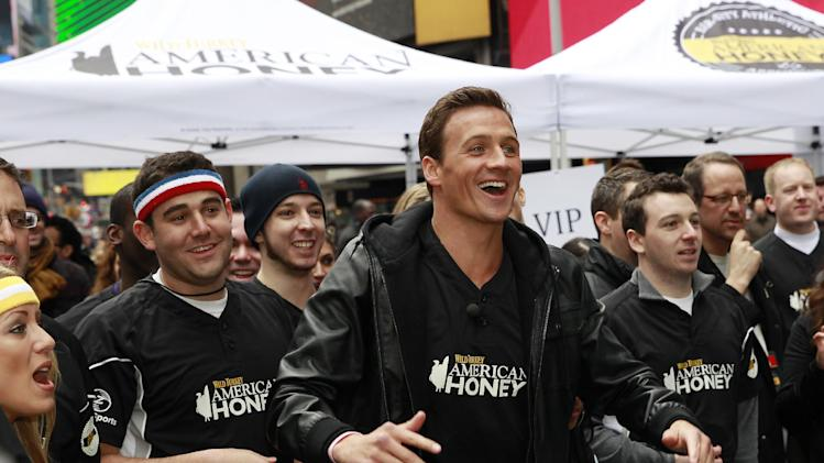 IMAGE DISTRIBUTED FOR AMERICAN HONEY - Eleven time Olympic medalist and TV star Ryan Lochte cheers his team on at the first ever American Honey Bar-sity Athletics kickball game in Times Square, on Tuesday, April, 23, 2013 in New York City, New York. (Photo by Mark Von Holden/Invision for American Honey/AP Images)