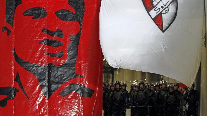 Anti riot police officers in full gear stand behind a giant banner with the face of Benfica's legend soccer player Eusebio at the end of a Portugal Cup semifinal second leg soccer match between Benfica and Porto at Benfica's Luz stadium in Lisbon, Wednesday, April 16, 2014. Benfica won 3-2 on aggregate and will play the final