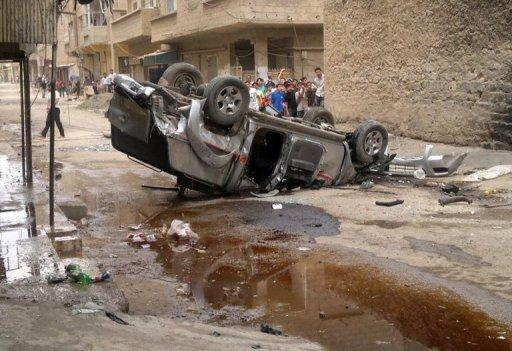 Syrians inspect a vehicle damaged in clashes in Deir Ezzor