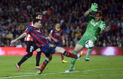 FC Barcelona's Lionel Messi, from Argentina, left, duels for the ball against Athletic Bilbao's goalkeeper Gorka Iraizoz during a Spanish La Liga soccer match at the Camp Nou stadium in Barcelona, Spain, Sunday, April 20, 2014