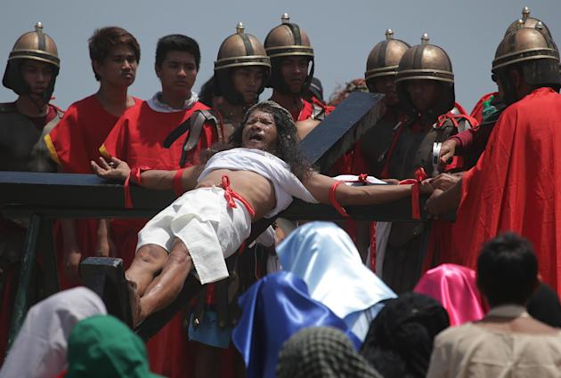 Filipino devotee Ruben Enaje shouts in pain as he is nailed to a cross to re-enact the crucifixion of Jesus Christ in San Pedro Cutud village, Pampanga province, northern Philippines on Friday, April