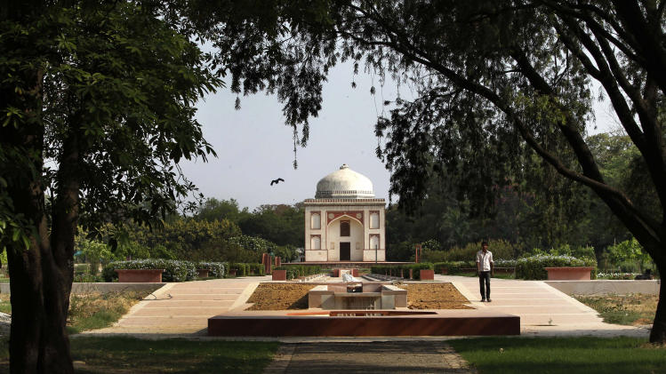 In this Wednesday, June 5, 2013 photo, a worker walks past a renovated tomb inside Sunder Nursery, a 100-acre field founded by British colonists to grow experimental plants, in New Delhi. (AP Photo/Manish Swarup)