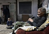 An elderly woman and her grandson sits outside their home in Miskolc, Hungary on April 22, 2012. The National Food Bank says that without its help 210,000 families in Hungary would struggle to put food on the table, a 30% increase from last year