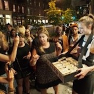 Top model Karlie Kloss (R) hawking her own Karlie's Kookies outside the DKNY boutique in the Soho district of New York City on September 6, 2012 during Fashion's Night Out