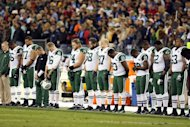 The New York Jets stand on the sideline in a moment of silence on December 17, 2012 for the victims of the mass shooting in Newtown, prior to the game against the Tennessee Titans. US athletes were quick to denounce the massacre, but a string of shootings involving star players indicates that many are avid gun owners who pack their heat wherever they go