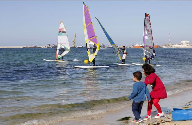 Children on the beach watch as Libyans take part in a local windsurfing competition in Tripoli