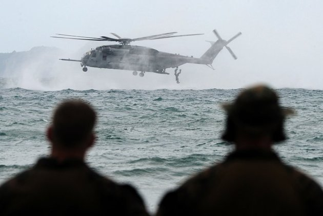 A helicopter hovers above the sea before it drops US and Philippine Marines during helocast training as part of the annual joint Philippine-US military exercises at the Philippine Marine base in Ternate, Cavite province, southwest of Manila on September 20, 2013