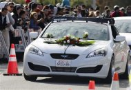 "A vehicle with flowers placed on the hood is driven past a crowd attending an unofficial memorial event for ""Fast & Furious"" star Paul Walker in Santa Clarita, California December 8, 2013. REUTERS/Jonathan Alcorn"