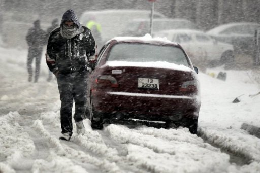 A Jordanian man walks past a vehicle as snow falls over Amman on January 9, 2013. The worst storms in a decade left swathes of Israel and Jordan under a blanket of snow and parts of Lebanon blacked out, bringing misery to a region accustomed to temperate climates.