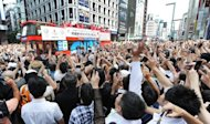 Japan's medallists (L) at the London 2012 Olympic Games wave to a crowd of people from open-top buses during a parade at Tokyo's upmarket Ginza street on August 20, 2012