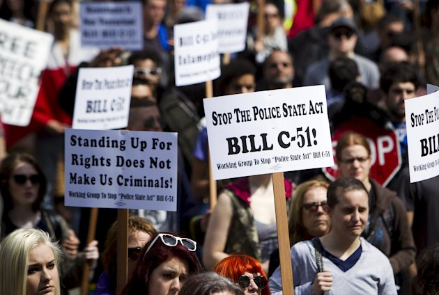 Protesters hold signs during a demonstration against Bill C-51, the Canadian federal government's proposed anti-terrorism legislation in Vancouver, British Columbia April 18, 2015. REUTERS/Ben Nelms