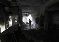 A Free Syrian Army fighter holding a weapon walks inside a damaged house in Deir al-Zor, eastern Syria November 14, 2013. Picture taken November 14, 2013. REUTERS/Khalil Ashawi