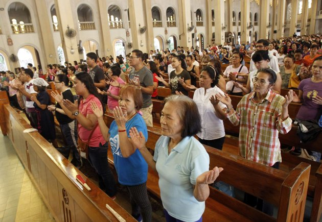 Catholics recite the Lord's Prayer during mass in the Mother of Perpetual Help church in Paranaque city, metro Manila September 7, 2013. Pope Francis has urged the international community to join in a special day of fasting and prayer for peace in Syria on Saturday. REUTERS/Romeo Ranoco (PHILIPPINES - Tags: MILITARY RELIGION CIVIL UNREST CONFLICT POLITICS)