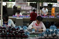 Workers make shoes at a factory in China's Fujian province. There was a double-digit increase in production at factories, workshops and mines for the first time since March, the National Bureau of Statistics said