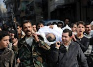 Syrians carry a body of a fighter during his funeral in the northeastern city of Aleppo on February 15, 2013. Syrian rebels captured a military airbase in the north and geared up for a major battle against loyalists as the opposition said it refuses to accept President Bashar al-Assad in talks on the 23-month conflict
