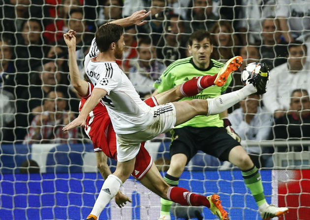 Bayern's Thomas Mueller challenges for the ball with Real's Xabi Alonso during a first leg semifinal Champions League soccer match between Real Madrid and Bayern Munich at the Santiago Bernabe
