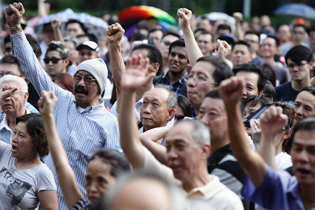 SINGAPORE - JUNE 07: People react to speaker speech during the 'Return Our CPF' protest at the Speakers' Corner at Hong Lim Park on June 7, 2014 in Singapore. The protest was staged to demand greater transparency and accountability from the government on how the CPF monies are being utilized. (Photo by Suhaimi Abdullah/Getty Images)