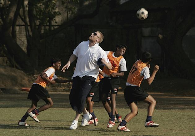 MUMBAI (BOMBAY), INDIA - FEBRUARY 17:  Andrew Flintoff of England plays football with local children during  a visit the Magic Bus Child development program in Lower Parel, on February 17, 2006 in Mum