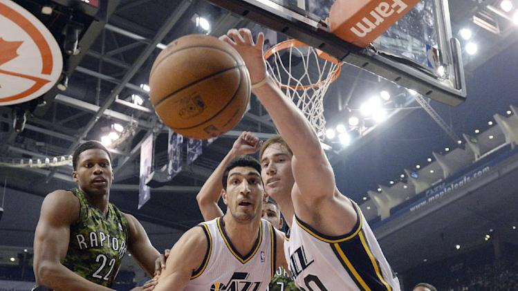 Utah Jazz center Enes Kanter (0) and teammate Gordon Hayward, right, battle Toronto Raptors' Rudy Gay for the ball during the first half of an NBA basketball game in Toronto on Saturday, Nov. 9, 2013