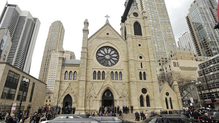 Mourners leave Holy Name Cathedral after film critic Roger Ebert's funeral in Chicago, April 8, 2013. The Pulitzer Prize winning movie reviewer died Thursday, April 4 at age 70 after a long battle with cancer. (AP Photo/Paul Beaty)