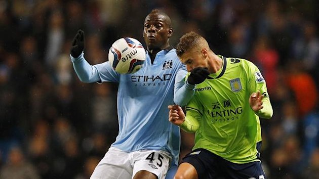 Manchester City's Mario Balotelli (L) challenges Aston Villa's Joe Bennett during their English League Cup soccer match at The Etihad Stadium in Manchester, northern England, September 25, 2012