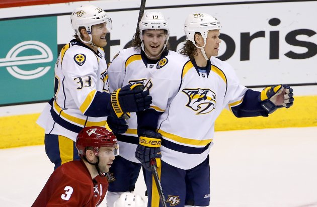 Nashville Predators' Olli Jokinen, right, of Finland, celebrates his goal against the Arizona Coyotes with teammates Calle Jarnkrok (19), of Sweden, and Colin Wilson (33) as Coyotes' Keith Yandle (3) skates past during the third period of an NHL hockey game Thursday, Dec. 11, 2014, in Glendale, Ariz. The Predators defeated the Coyotes 5-1. (AP Photo/Ross D. Franklin)