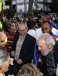 Fidel Castro (bottom R) speaks to Cubans at a polling station in Havana in this photo from AIN taken on February 3, 2013. The ailing revolutionary leader made a surprise appearance in Havana to vote in parliamentary polls, expressing confidence in the revolution despite a decades-long US trade embargo