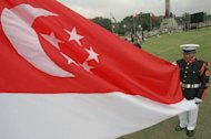 This file illustration photo shows a Philippines military holding Singapore's national flag during a ceremony for the 23rd SEA Games in Manila, in 2005. The Philippines is studying a military training agreement with Singapore and is closely watching the progress of a similar accord with Australia for lessons, the defence department said on Saturday