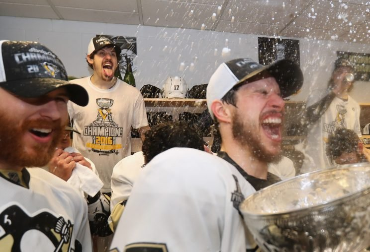 SAN JOSE, CA - JUNE 12: Evgeni Malkin #71 and Sidney Crosby #87 of the Pittsburgh Penguins celebrates with the Stanley Cup in the locker room after winning Game 6 of the 2016 NHL Stanley Cup Final over the San Jose Sharks at SAP Center on June 12, 2016 in San Jose, California. The Penguins won the game 3-1 and the series 4-2. (Photo by Dave Sandford - Pool/Getty Images)