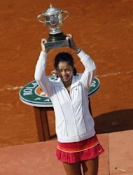 China's Li Na poses with the trophy after defeating Italy's Francesca Schiavone in their Women's final of the French Open tennis championship at the Roland Garros stadium, in Paris, June 2011. Her straight sets demolition of defending champion Schiavone made her the first Asian player to win a Grand Slam singles title