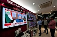 People watch a televised speech by Indian Premier Manmohan Singh in New Delhi. While political opponents accused Singh of selling out the country to foreign interests, the media lauded him for addressing the difficulties facing Asia's third-largest economy