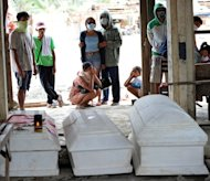 Residents stand next to coffins of deceased relatives who died during flash floods caused by Typhoon Bopha in New Bataan in Compostela Valley province on December 8. While the powerful typhoon had weakened to a tropical storm, it was still causing downpours in the north