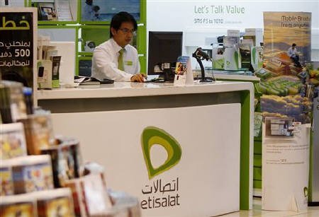 An employee sits behind the counter of an Etisalat telecom kiosk in a shopping mall in Dubai, May 18, 2011. REUTERS/Jumana El Heloueh/Files