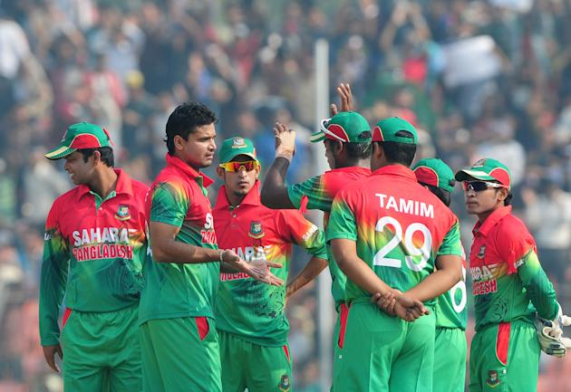 Bangladesh cricketer Mashrafe Bin Murtaza (2L) celebrates with teammates after the dismissal of the unseen West Indies batsman Lendl Simmons during the first one day international cricket match betwee