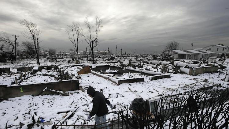 Damon Rasinya carts debris from his family home past the fire-scorched landscape of Breezy Point after a Nor'easter snow, Thursday, Nov. 8, 2012 in New York.  The beachfront neighborhood was devastated during Superstorm Sandy when a fire pushed by the raging winds destroyed many homes.  (AP Photo/Mark Lennihan)