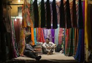 Indian sari vendors share a light moment in the Old Quarters in New Delhi on January 30, 2013. India's economy should return to a high-growth path of seven to eight percent in the next couple of years, picking up from decade-low expansion, the finance minister said on Saturday