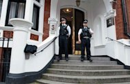 Metropolitan Police Officers wait outside the main door of the Ecuadorian embassy in London. Ecuador said it will announce its decision on granting asylum to WikiLeaks founder Julian Assange on Thursday, setting up a showdown with Britain, which vowed to extradite him to Sweden