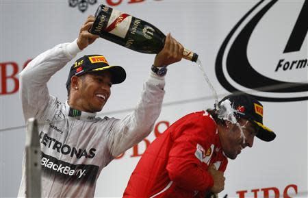 First-placed Mercedes Formula One driver Hamilton pours champagne on third-placed Ferrari Formula One driver Alonso as he celebrates his win at the Shanghai International Circuit