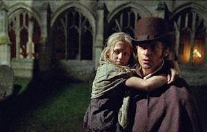 "This film image released by Universal Pictures shows Hugh Jackman as Jean Valjean holding Isabelle Allen as Young Cosette in a scene from ""Les Miserables."" (AP Photo/Universal Pictures, Laurie Sparham)"