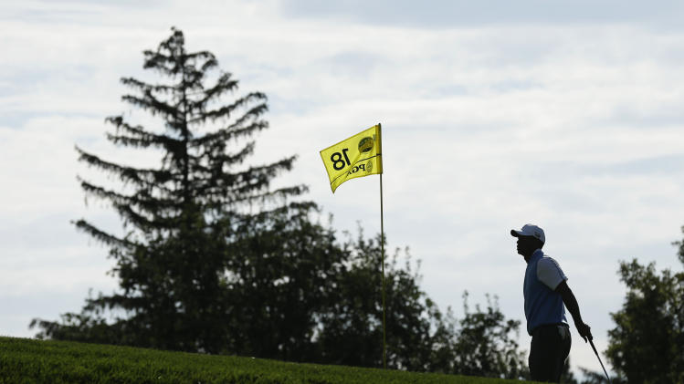 Tiger Woods walks on the 18th green during a practice round for the PGA Championship golf tournament at Oak Hill Country Club, Tuesday, Aug. 6, 2013, in Pittsford, N.Y. (AP Photo/Charlie Neibergall)